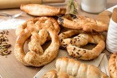 面包、椒盐脆饼和酥皮点心产品、麦子和面粉在木厨房用桌上 库存图片