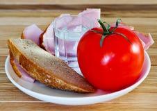 面包、肉、蕃茄和一杯伏特加酒 库存图片