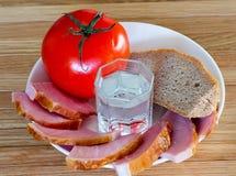 面包、肉、蕃茄和一杯伏特加酒 免版税图库摄影