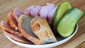 面包、肉和腌汁在一块白色板材 库存图片