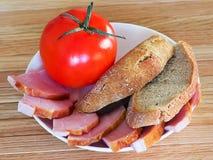 面包、肉和蕃茄在白色板材 图库摄影