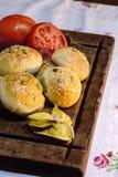 面包、蕃茄和大蒜在黑暗的木桌上 库存照片