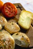 面包、蕃茄和手工制造乳酪在黑暗的木桌上 免版税库存图片