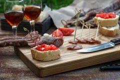 面包、香肠、红葡萄酒、玻璃、切板和刀子在一顿快餐的一张木桌上安排了在乡下 免版税库存照片
