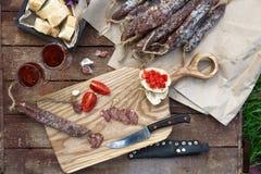 面包、香肠、红葡萄酒、玻璃、切板和刀子在一顿快餐的一张木桌上安排了在乡下 库存图片