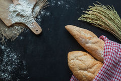 面包、麦子和面粉在黑黑板,面包店背景 库存图片