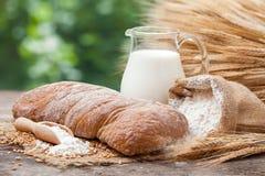 面包、水罐牛奶,大袋用面粉和捆麦子 免版税库存照片
