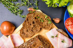 面包切片顶视图在木砧板的用草本、火腿和菜 免版税库存图片