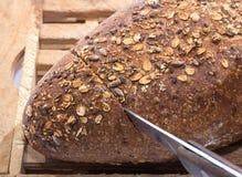 面包剪切全部谷物的刀子 免版税库存图片