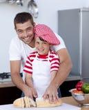 面包剪切父亲微笑的儿子 免版税图库摄影