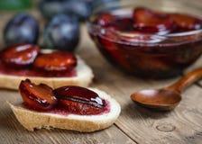 面包厚厚了地涂用与一把木匙子的李子果酱在葡萄酒桌上 免版税库存图片