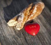 面包和红色心脏在木桌上 免版税库存照片