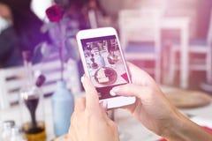 面包和酒妇女照相在她的智能手机在餐馆 免版税库存图片