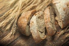 面包和麦子在木桌,浅DOF上 库存图片