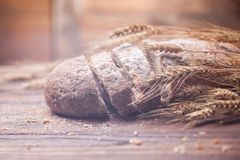 面包和麦子在木桌,浅DOF上 免版税库存图片