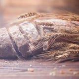 面包和麦子在木桌,浅DOF上 免版税库存照片