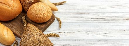 面包和麦子在白色木背景 做广告和设计的,与拷贝空间的电视节目预告顶视图横幅 库存图片