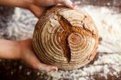 黑面包在手上 免版税库存图片