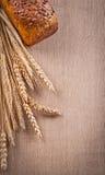 黑面包大面包与麦子耳朵的在木橡木 免版税库存照片