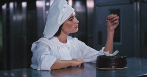 面包师成套装备的一狡猾的年轻女人在她的手和凝视上拿着一棵红色眼睛捉住的樱桃在它在奇迹 股票视频