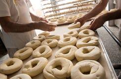 面包师面团为百吉卷做准备 免版税库存照片