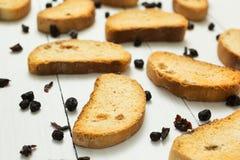 面包干用葡萄干和干莓果在白色木背景,饮食早餐 免版税库存照片