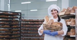 面包店产业有相当微笑新鲜的被烘烤的面包篮子的年轻女人面包师看直接对照相机和 股票视频