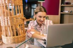 面包店兴旺的业主使用她的膝上型计算机的,当与供应商联系时 免版税库存图片