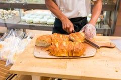 面包店切新鲜的有壳的面包在木bo的厨师手 库存图片