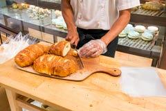 面包店切新鲜的有壳的面包在木bo的厨师手 免版税库存图片