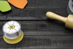面包店和烹调工具有厨房计时的在木桌上 免版税图库摄影