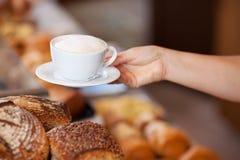 面包店工作者服务热奶咖啡 免版税库存照片