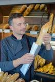 面包店店主骄傲的面包生产 库存照片