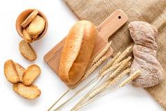 面包店设置了用在桌白色背景顶视图的新鲜的小麦面包 免版税库存图片