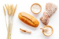 面包店设置了用在桌白色背景顶视图的新鲜的小麦面包 图库摄影