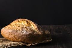 面包店-金土气有壳的面包和小圆面包在黑背景 免版税库存照片