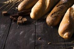 面包店-金土气有壳的面包和小圆面包在黑黑板背景 免版税库存照片