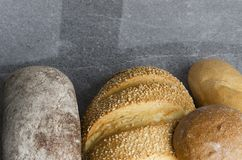 面包新近地被烘烤的不同形式在灰色桌上的 免版税库存照片