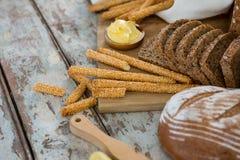 面包条和面包切片用黄油在切板 库存图片