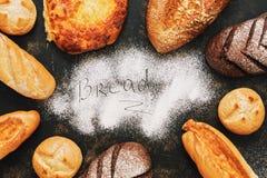 面包框架  在面粉的词面包 各种各样的面包的一汇集在土气背景的 在视图之上 复制空间 库存照片