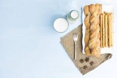 面包棒和牛奶在天蓝色制表背景 与膳食的快餐 库存照片