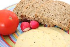 面包片、蕃茄、乳酪和萝卜在板材 库存图片