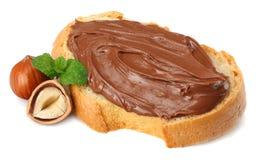 面包片与巧克力奶油的用在白色背景隔绝的榛子 免版税库存照片