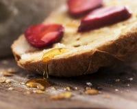 面包片与蜂蜜垂度和草莓的 免版税库存照片