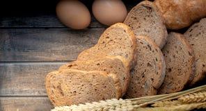 面包片和两个鸡蛋在木桌上 免版税库存照片