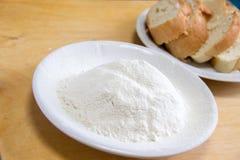 面包片和小麦面粉在一块白色板材在桌上 库存照片