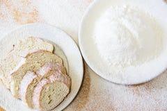面包片和小麦面粉在一块白色板材在桌上 库存图片