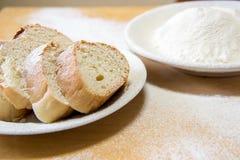 面包片和小麦面粉在一块白色板材在桌上 免版税库存照片