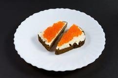面包片涂油了与油和红色鱼子酱在一个白色茶碟 免版税图库摄影