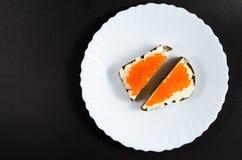 面包片涂油了与油和红色鱼子酱在一个白色茶碟 免版税库存图片